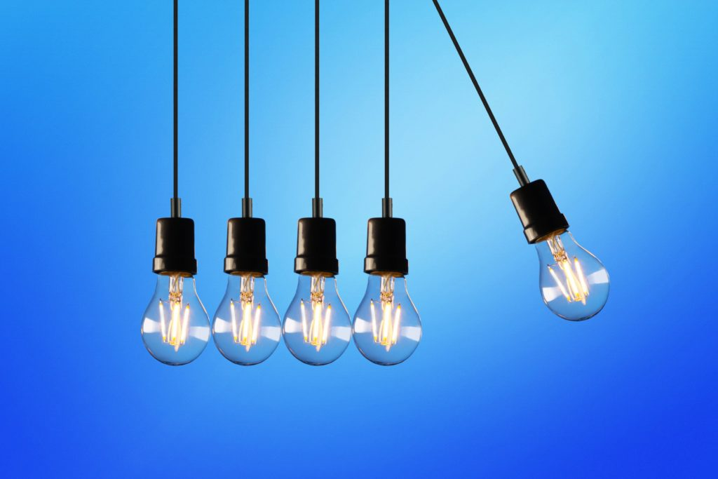 5 light bulbs hanging in front of blue background.